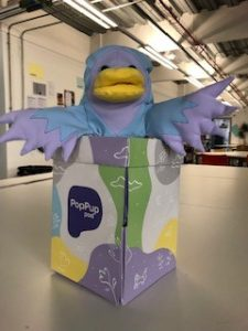Bo the puppet (a light blue and light purple bird) sat in the PopPupPod box.