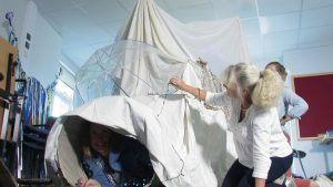 A woman coming out of a tunnel covered in a white sheet.