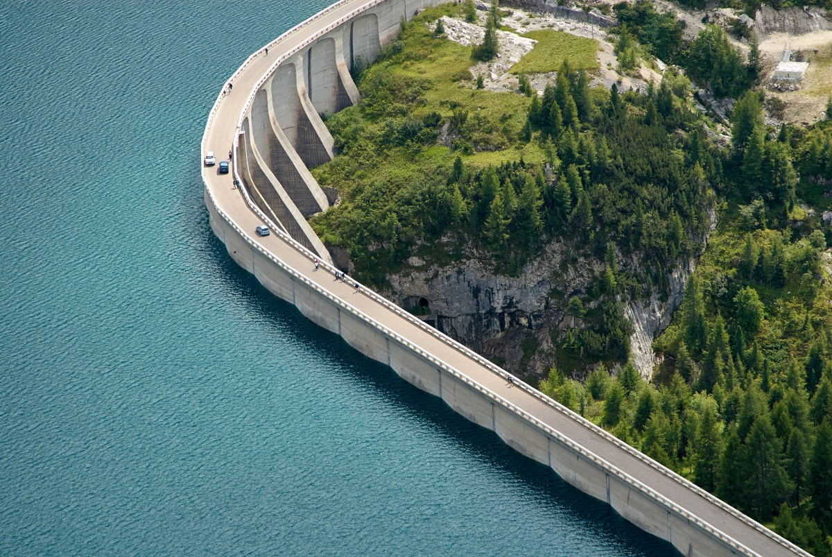 Cars and people walking on a dam