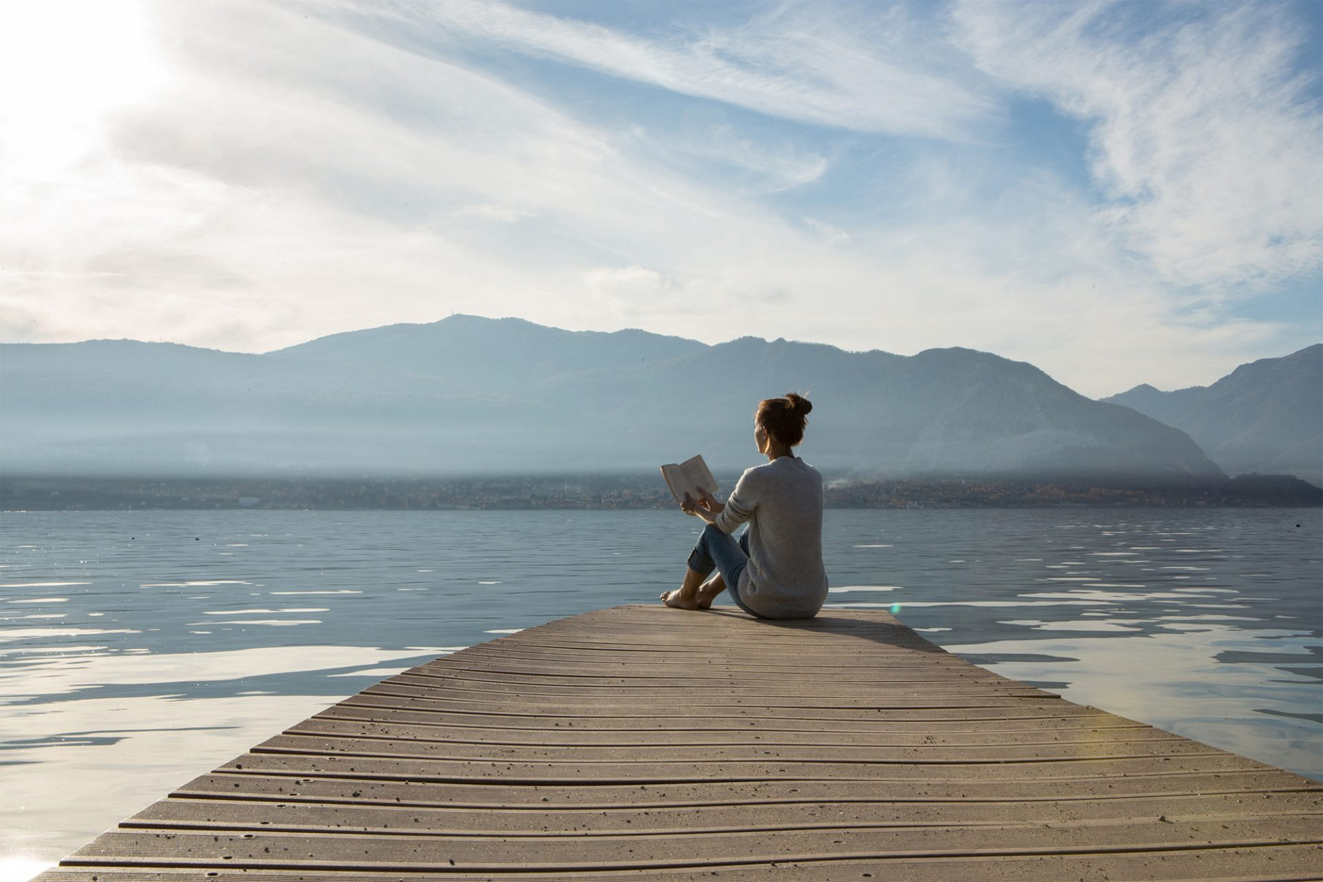 Woman sitting on a pier reading a book